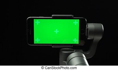 Steadicam stabilizer with a green screen on smartphone is moving from the left side of a shield to the center. Professional equipment for a filmmaker. Close-up motion on black background.