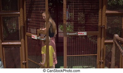 Steadicam shot of a young woman and her little son visiting a bird park