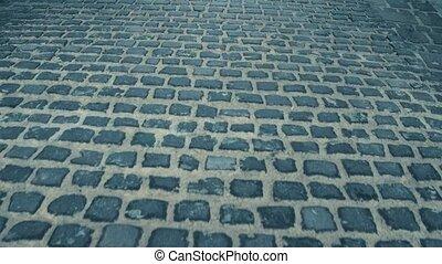 Steadicam shot of ancient urban pavement.