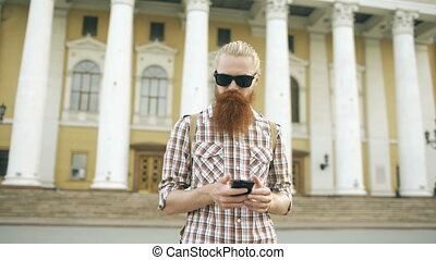 Steadicam shot of Bearded tourist man lost in city and using...