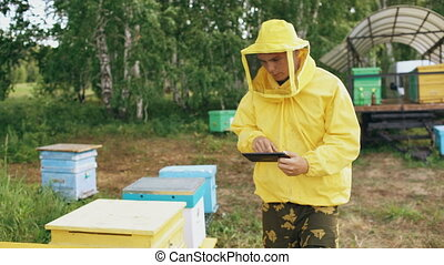 Steadicam shot of Beekeeper man with tablet computer checking beehives in apiary