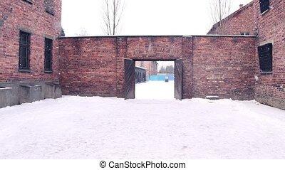 Steadicam shot of concentration camp brick building in falling snow. 4K clip
