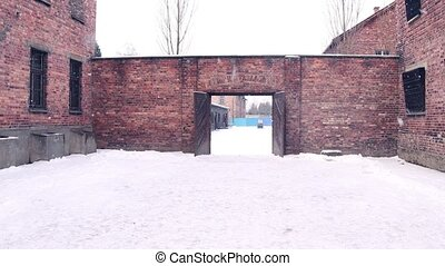 Steadicam shot of concentration camp brick building in falling snow. 4K clip