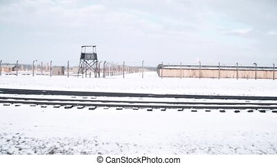 Steadicam shot of concentration camp fence, guard tower and railroad tracks in winter. 4K video