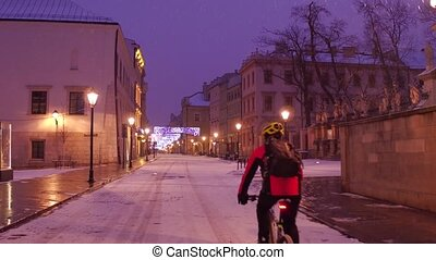 Steadicam shot of Krakow old town street and lonely biker riding in the snow. 4K video