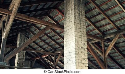Steadicam shot of old building sloped roof. View from inside.