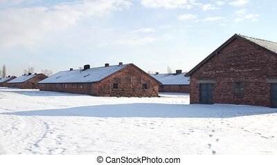 Steadicam shot of old concentration camp brick barracks in winter. 4K video