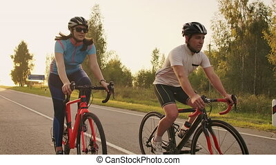 Steadicam shot of two healthy mem and woman peddling fast with cycling road bicycle at sunset