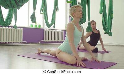 Two flexible women doing yoga exercises in nice studio -...