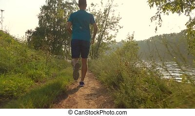 Steadicam video of athletic man running along forest path,...