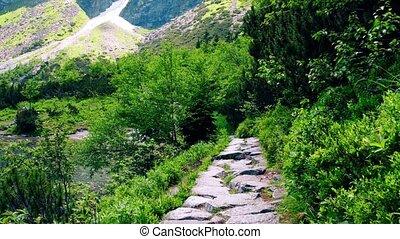 Steadicam walk along mountainous lake rocky path - Steadicam...