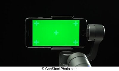 Steadicam gimbal stabilizer with a green screen on smartphone is rising up and falling down. Professional equipment for the filmmaker. Anti shake , anti vibration. Close-up motion on black background.