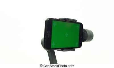 Close-up motion of steadicam with a smartphone for shooting smooth video is turning it's green screen to the camera. Professional equipment for filmmaker isolated on white. Anti vibration, anti shake.