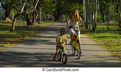 steadycam shot of a young woman and her little son riding a bicycle and runbike in a tropical park