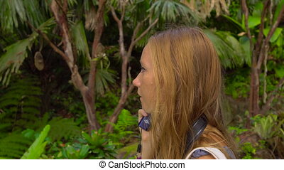 Steadycam shot of a young woman in a tropical garden uses an electronic audio guide.