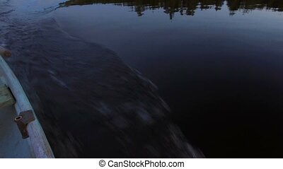 Steadycam shot of motorboat driving in th evening