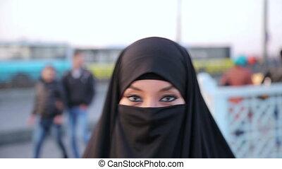 Steadycam - Woman dressed with black headscarf, chador walking, istanbul