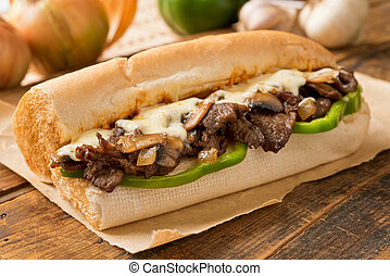 A delicious oven baked steak and cheese submarine sandwich with mushrooms, green peppers, and onion.