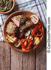 Steak and grilled vegetables with pesto closeup. vertical top view