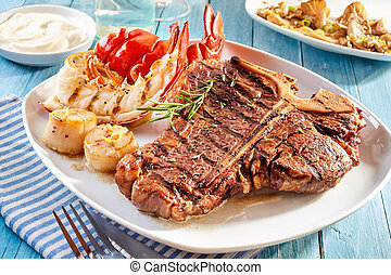 Steak and lobster meal with side dishes - Prepared surf and ...