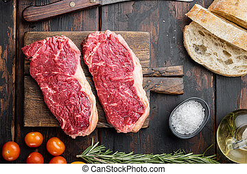 Steak burger ingredients with beef marbled meat, on dark wooden background, top view