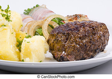 steak dinner with potatoes and vegetables in bacon