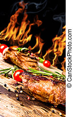 Steak - Grilled beef steaks with flames on background