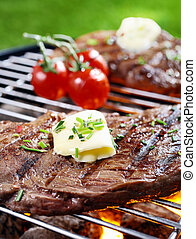 Closeup of a tender succulent portion of steak seasoned with butter and herbs grilling over a fire in a portable barbecue on a lawn