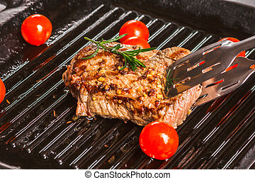 steak holding forceps and cherry tomatoes in a pan