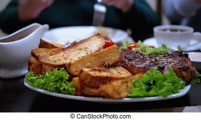 Steak on Ribs with Potatoes and Salad on a Table in a Georgian Restaurant