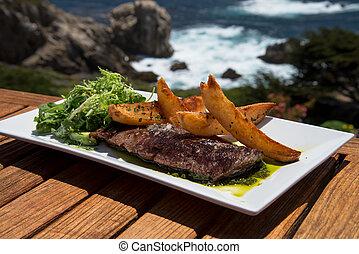 Steak, potatoes, salad on plate