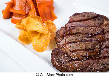 Steak rib-eye garnished with grilled vegetables and crisp on white plate. Close up