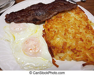 Steak ribs with two eggs over easy Hash-brown potatoes on a ...