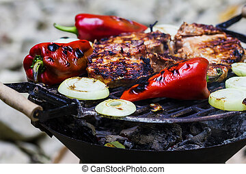 Steak, sausage, onion, red pepper and toast on a BBQ