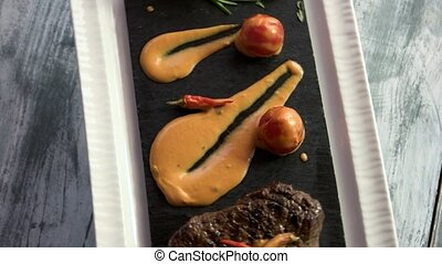 Steak with cognac sauce. Food on gray wood background.