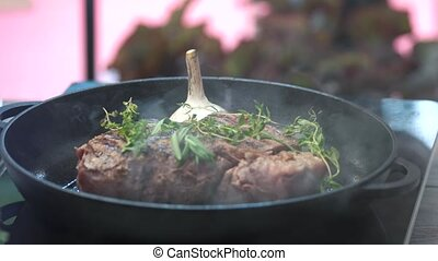 Steak with herbs on pan.