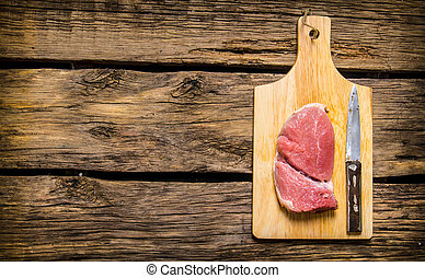 Steaks from raw meat with a butcher knife.