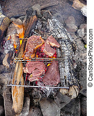 Steaks grilling on wire racks outdoors