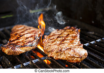 Steaks on barbecue - Beef steaks cooking in open flame on...