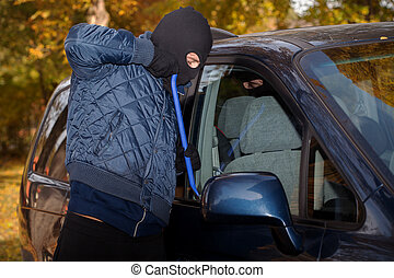 Stealing a car - A masked thief striving to steal a big car