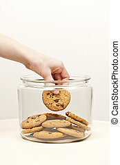 Stealing cookies from the cookie jar - Hand taking chocolate...