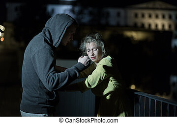 Stealing woman's earings - Young man is stealing scared ...