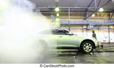 Steam clubs cover car which is washed on car wash with workers