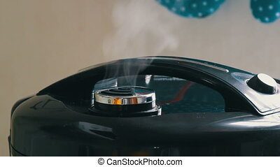 Steam comes out of the lid of the black multicooker