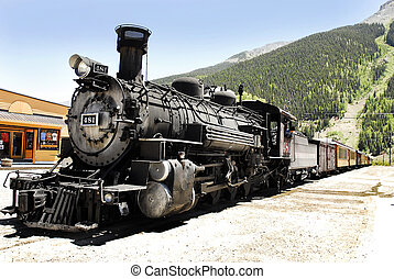 A vintage stam engine and train idles on the tracks in a small western town