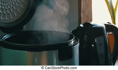 Steam in a cooking multicooker with an open lid in the kitchen