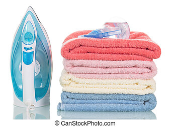 Steam iron and colorful towels isolated on white background.