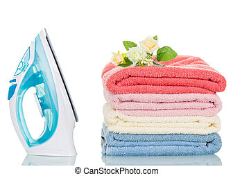 Steam iron and colorful towels isolated on white
