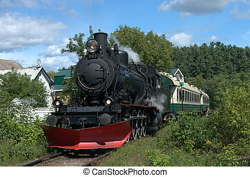 A passenger train with 2 carriages, pulled by an steam locomotive built in 1907.