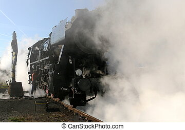 Steam locomotive refilling water in the station